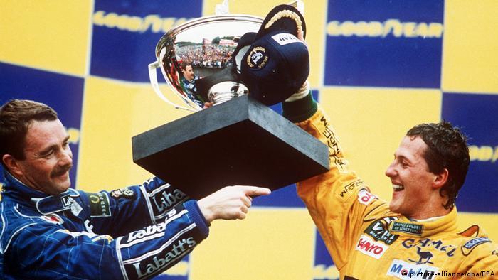 Nigel Mansell (esq.) levanta taça com Michael Schumacher (dir.), de macacão amarelo