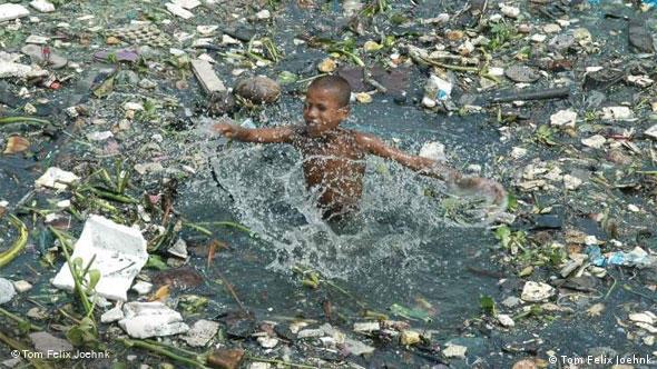 Kind spielt in dreckigem Fluss (Foto: Tom Felix Joehnk)