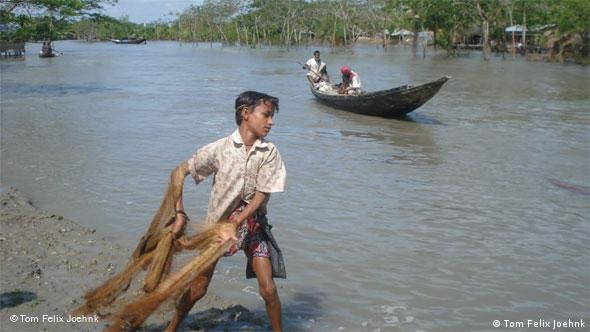 A boy throwing a net into a river in Bangladesh