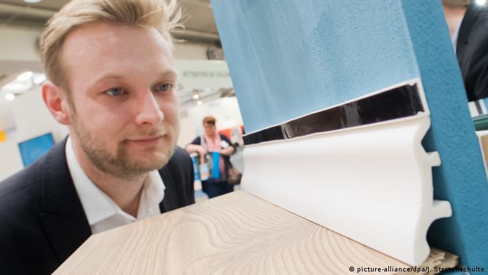 Ein Mann schaut sich das Modell einer Bodenfußleiste an (Foto: Picture Alliance)