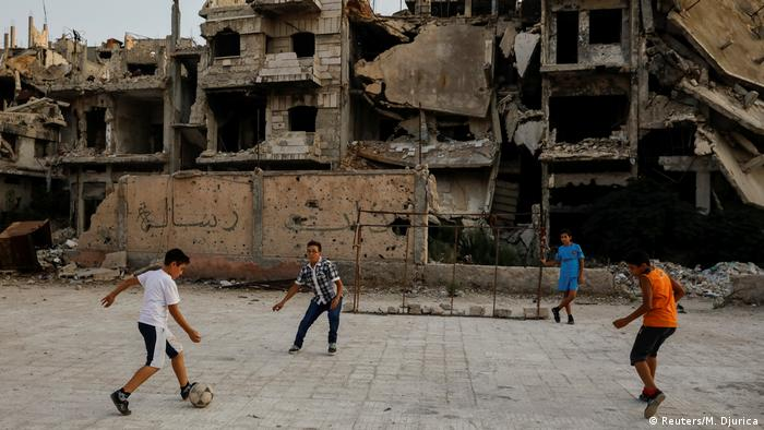 Children play soccer amid ruins