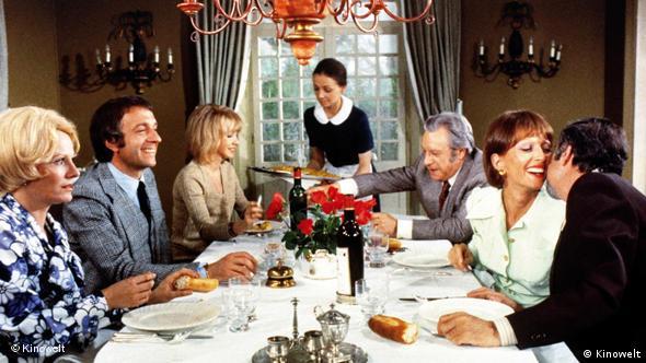 Die Abendgesellschaft zu Tisch - sechs Personen und eine Bedienstete um einen gedeckten Tisch (Kinowelt/Arthaus)