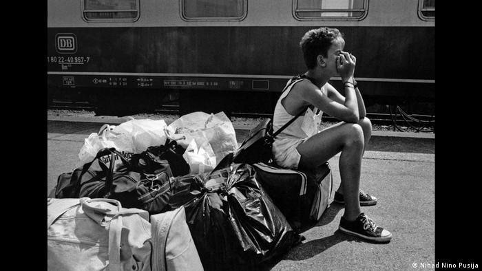 Dječak sjedi na torbi na peronu i čeka voz