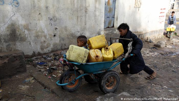 Yemen children cart water containers through the streets of Sanaa