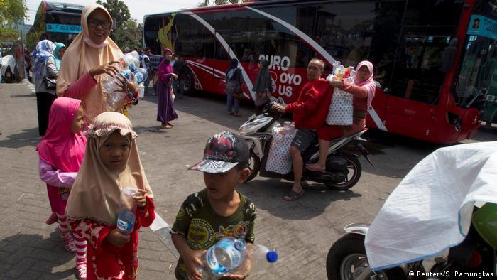 Penduduk Surabaya mengantri untuk membeli tiket bus dengan memberikan botol plastik bekas (Reuters/S. Pamungkas)
