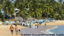 Tourists stroll whilst local fishermen work on this popular surf beach, Arugam Bay, Eastern Province, Sri Lanka, Asia | Verwendung weltweit, Keine Weitergabe an Wiederverkäufer.
