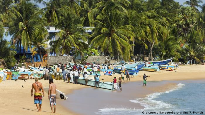 Tourists stroll as local fishermen work on a popular surf beach in Sri Lanka.
