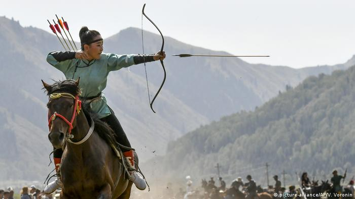 A women releases an arrow during an archery competition during the Third Nomad Games in Kyrgyzstan.