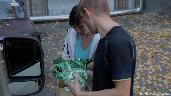 Волонтер принимает пластиковый мусор