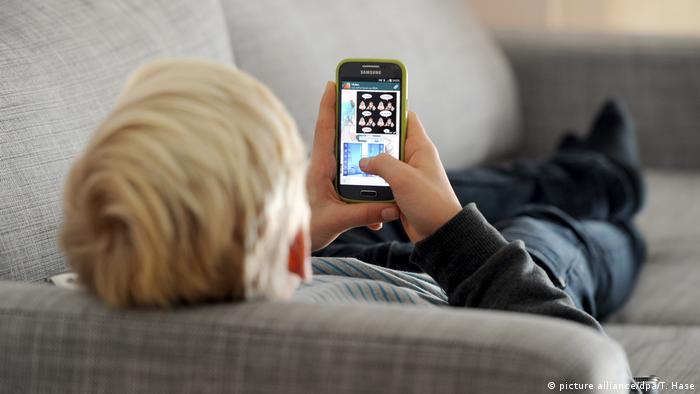 Blonder Jugendlicher liegt auf grauer Couch mit einem Smartphone in der Hand (Foto: picture alliance/dpa/T. Hase).