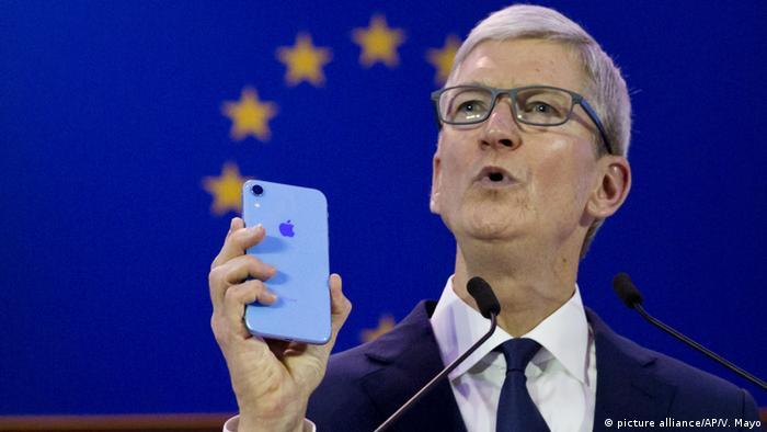Тим Кук держит iPhone на фоне флага Евросоюза