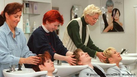 Drei Frauen stehen an Waschbecken und waschen drei anderen Frauen die Haare (picture-alliance/ZB/B. Wüstneck)