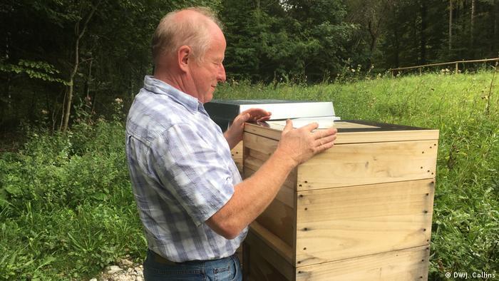 Ein Mann, der an einem Bienenstock steht.