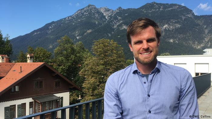 A man with a house and mountains in the background