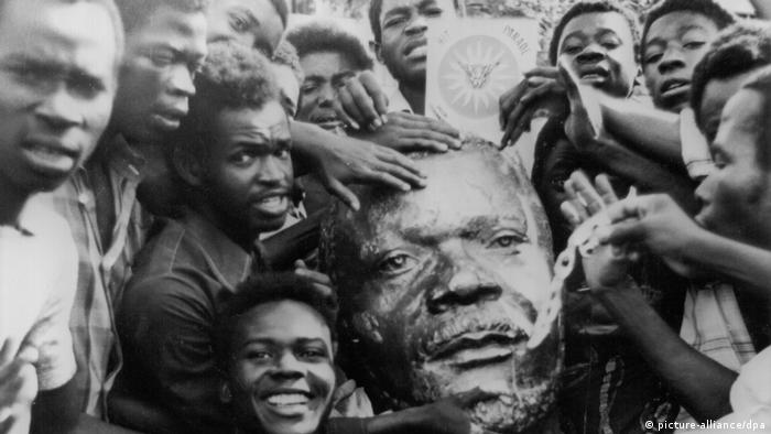 Des hommes portant la tête d'une statue de Bokassa brisée après son renversement