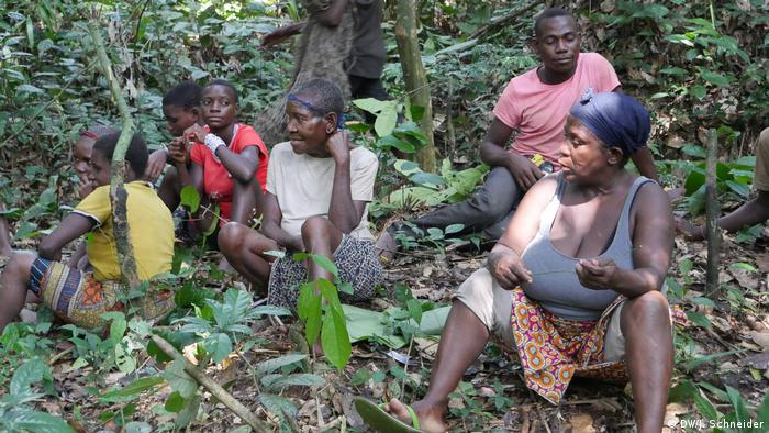 Relatives of the indigenous BaAka sit in the forest