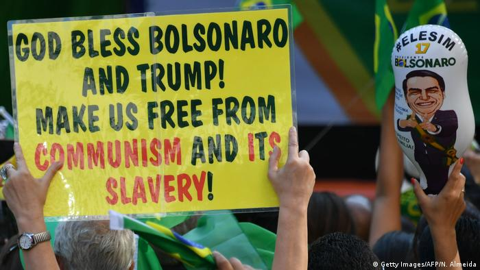 A supporter of right-wing Brazilian presidential candidate, Jair Bolsonaro, holds up a yellow sign which reads 'God bless Bolonaro and Trump! Make us free from communism and its slavery!'