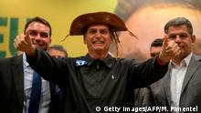 TOPSHOT - Brazil's right-wing presidential candidate for the Social Liberal Party (PSL) Jair Bolsonaro (C) gestures flanked by his son and Rio de Janeiro's elected Senator Flavio Bolsonaro (L) and the president of the Social Liberal Party (PSL) Gustavo Bebianno during a press conference in Rio de Janeiro, Brazil on October 11, 2018. - The far-right frontrunner to be Brazil's next president, Jair Bolsonaro, stumbled Wednesday by spooking previously supportive investors, while a spate of violent incidents pointed to deep polarization caused by the election race. (Photo by Mauro Pimentel / AFP) (Photo credit should read MAURO PIMENTEL/AFP/Getty Images)