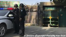 In this Nov. 2, 2017 photo, police officers on duty in the vicinity of a center believed to be used for re-education in Korla in western China's Xinjiang region. Authorities are using detentions in political indoctrination centers and data-driven surveillance to impose a digital police state in the region of Xinjiang and its Uighurs, a 10-million strong, Turkic-speaking Muslim minority Beijing fears could be influenced by extremism. (AP Photo/Ng Han Guan) |