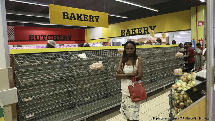 A Zimbabwean woman stands at an empty grocery shelf