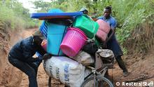 Congolese migrants expelled from Angola attempt to push a rented bicycle to transport their belongings along the dirt road to Tshikapa, Kasai province near the border with Angola, in the Democratic Republic of the Congo, October 12, 2018. Picture taken October 12, 2018. REUTERS/Giulia Paravicini