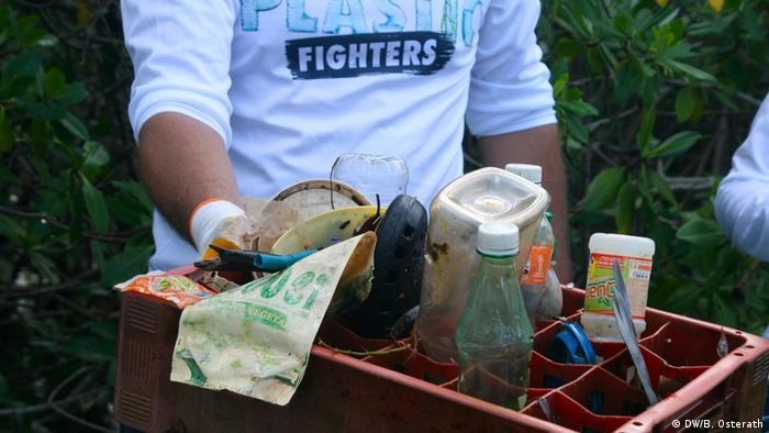 A volunteer wearing shirt which reads 'Plastic Fighters' carrys a container containing various pieces of plastic trash collected from the beach on Roatan