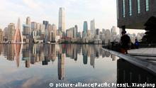Reflection of skyscrapers can be seen at a pond of a bank near the Qiansimen Bridge in southwest China's Chongqing. (Photo by SIPA ASIA / Pacific Press) | Verwendung weltweit, Keine Weitergabe an Wiederverkäufer.