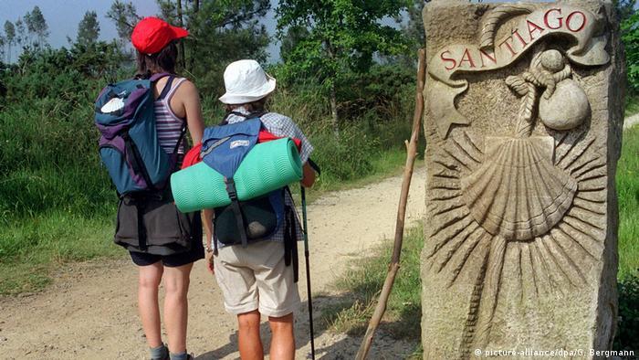 Zwei Pilger stehen mit Rucksäcken und Stöcken stehen vor dem steinernen Ortschild von Santiago de Compostela auf dem Jakobsweg