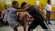 Girls practice self defence methods during a session with NGO Action Breaks Silence (ABS) called 'Empowerment through self-defence for women and girls' which aims to create a world free form fear of gender based violence, at Mbuyisa Makhubu Primary School in the are of Orlando West, in the South African township of Soweto, on October 10, 2018. - Official statistics suggest that more than 110 rapes are recorded by the police each day in South Africa. The figures are widely seen as inaccurate due to under-reporting. Some studies suggest only one in 13 rapes is reported to the police. (Photo by GULSHAN KHAN / AFP) (Photo credit should read GULSHAN KHAN/AFP/Getty Images)