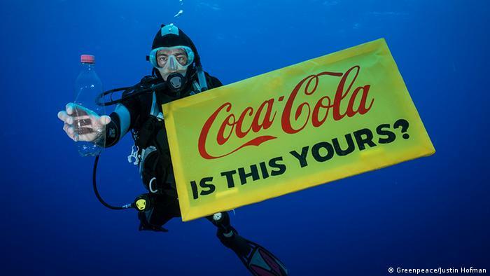 Мужчина под водой в костюме для подводного плавания держит пластиковую бутылку и табличку с надписью Coca-Cola, это ваше?