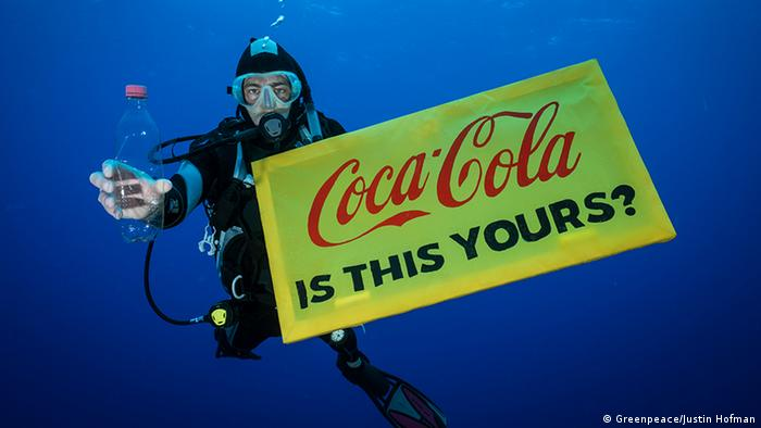A Greenpeace diver holds a banner reading 'Coca-Cola is this yours?' and a Coca-Cola bottle found adrift in the garbage patch