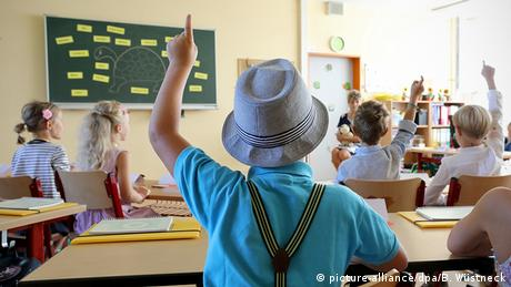 Kid in suspenders, polo shirt and a hat raises his hand in class