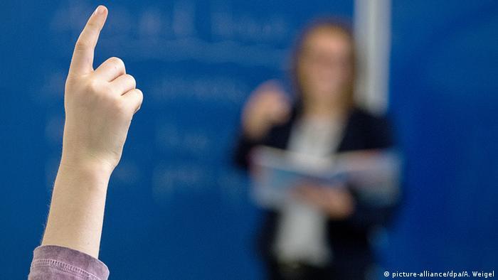 Aluno levanta a mão diante de professor