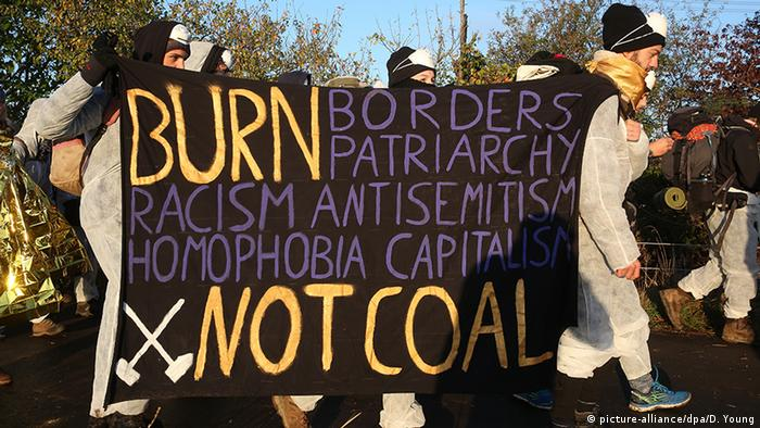 Environmental activists march together in direction of the Hambach open-pit coal mine carrying a sign reading Burn Borders, Patriarchy, Racism, Antisemitism, Homophobia, Capitalism, Not Coal (picture-alliance/dpa/D. Young)