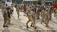17.10.2018, Indien, Nilackal: Ein Polizist wirft einen Stein, während eines Zusammenstoßes mit Demonstranten. Weil ein bedeutender Tempel im südlichen Indien für Frauen geöffnet werden sollte, haben Hindu-Hardliner protestiert und Journalistinnen und Pilgerinnen angegriffen.