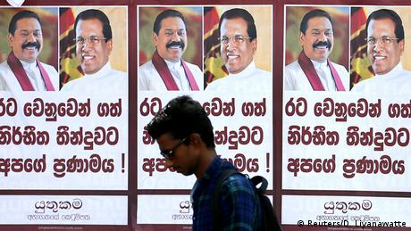 A man walks past posters of Sri Lanka's newly appointed Prime Minister Mahinda Rajapaksa and President Maithripala Sirisena (Reuters/D. Liyanawatte)