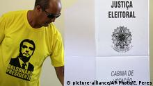 A voter dressed in a shirt with the image of the right-wing presidential candidate Jair Bolsonaro, votes in a polling station in a suburb of Brasilia, Brazil, Sunday, Oct. 28, 2018. (AP Photo/Eraldo Peres) |