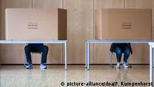 Zwei Wähler geben am 06.03.2016 in Frankfurt am Main (Hessen) in einem Wahllokal in einer Schule ihre Stimme ab. Rund 4,7 Millionen Hessen und 360.000 nichtdeutsche EU-Staatsbürger sind am 06.03.2016 zu den Kommunalwahlen in Hessen aufgerufen.