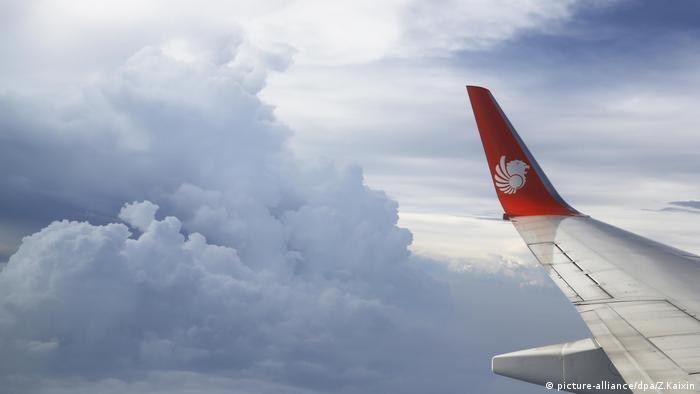 The wing of a jet plane of Indonesia's private airlines Lion Air is shown against the clouds