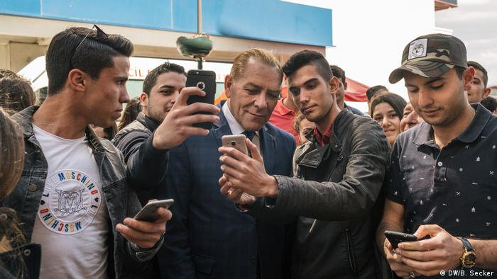 Men ask for selfies with Atatürk impersonator Göksal Kaya on a street in Izmir, Turkey.(DW/B. Secker)