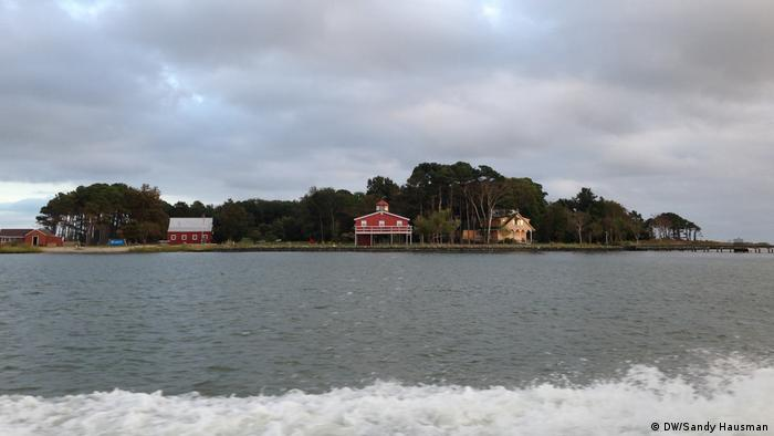 A small patch of land with trees and three houses, one of them on stilts, is seen from across the water
