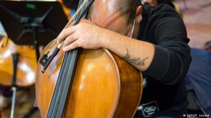 Cellist seems to nap over his instrument during rehearsal