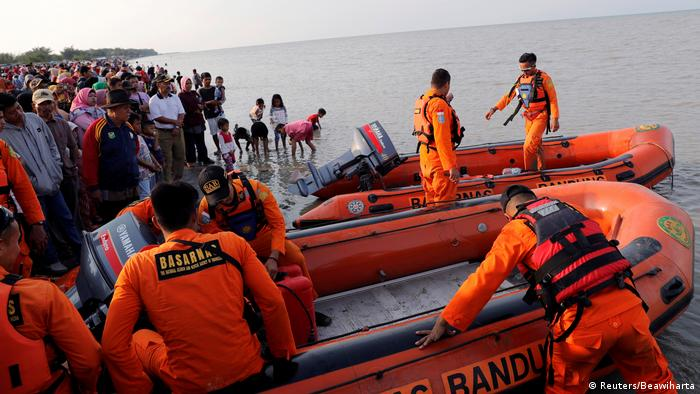 People watch on the beach, as a rescue team prepares their boat before looking for a crashed Lion Air jet