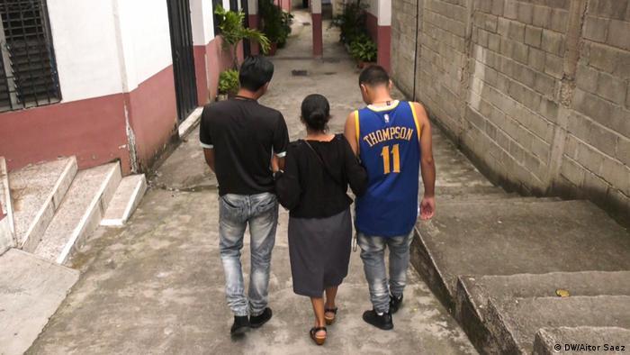 Dos hombres y una mujer caminan por un callejuela. (DW/Aitor Saez)