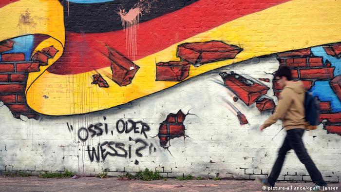 Графіті в Берліні, на якому зображений німецький прапор, який пробивається крізь мур