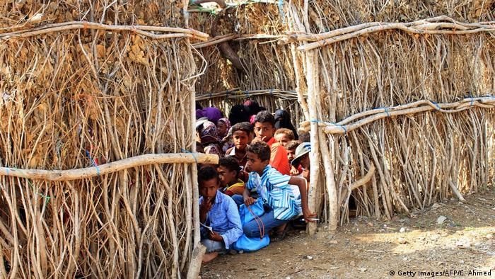 Children sit in a makeshift room