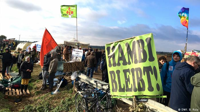 Zelený prapor s nápisem Hambach Forest zůstává v němčině na protestu proti uhlí v západním Německu