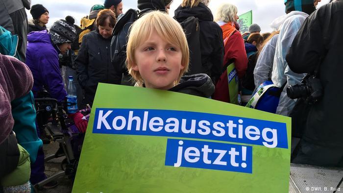 Na masovém protestu proti uhlí v západním Německu drží devítiletý chlapec ceduli, která říká, že uhlí je teď venku!