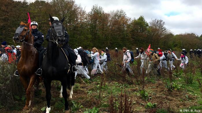 Demonstranti se blíží k lesu během masivní demonstrace proti uhlí v západním Německu.  Dva policisté na koních hlídají protestující a několik policistů pěšky