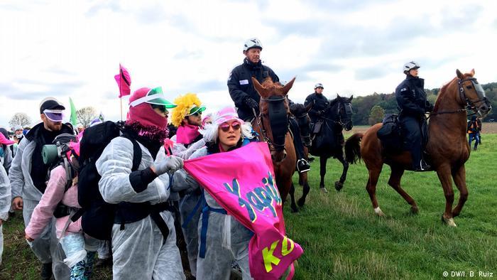 Policisté na koních pečlivě sledují demonstranty, kteří nosí křídla a bílé ochranné obleky